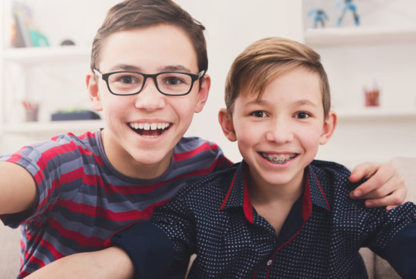 young children with braces smiling at camera